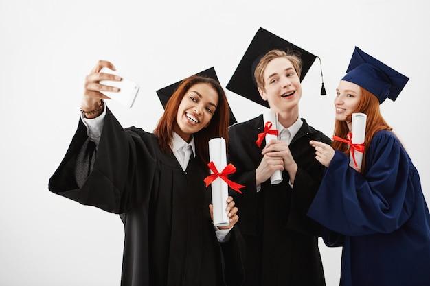 Drei internationale absolventenfreunde freuen sich über mäntel und machen ein selfie am telefon. zukünftige spezialisten haben spaß mit ihren diplomen.