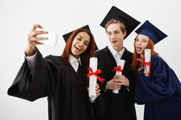 Drei internationale absolventenfreunde freuen sich über mäntel und machen ein selfie am telefon. zukünftige spezialisten oder mediziner, die spaß mit ihren diplomen über der weißen wand haben.