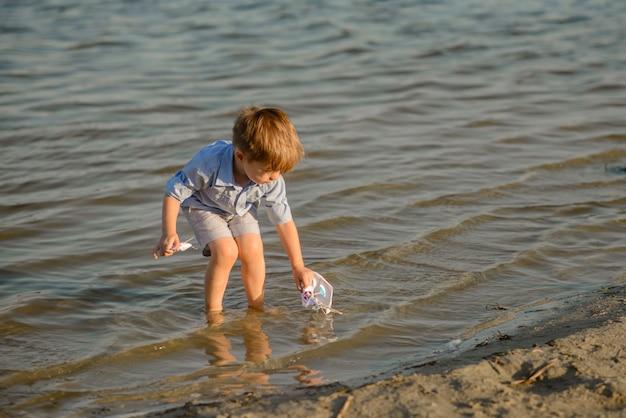 Drei jahre alten jungen spielen am strand. erholen sie sich in den sommerferien