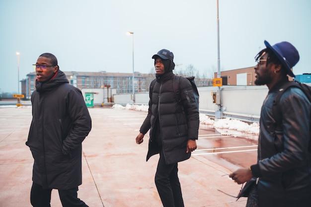 Drei junge afrikanische männer, die in die straße gehen und sprechen