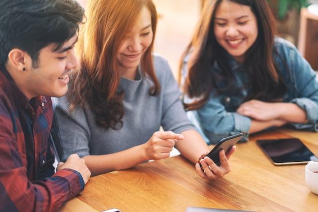Drei junge asiaten, die während eines meetings dasselbe handy benutzen und ansehen