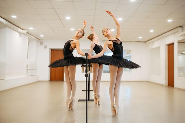Drei junge ballerinas, teenagerprobe in der barre im unterricht