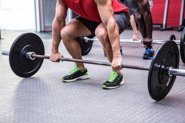 Drei junge bodybuilder, die gewichtheben tun