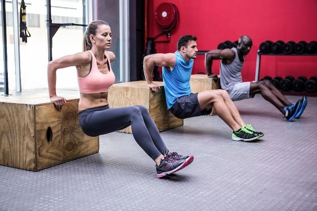 Drei junge bodybuilder, die übungen machen
