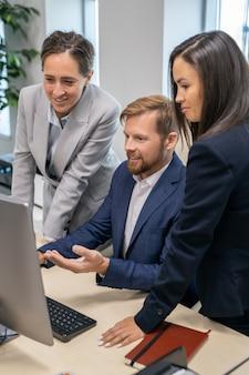 Drei junge büroangestellte, die auf computerbildschirm schauen