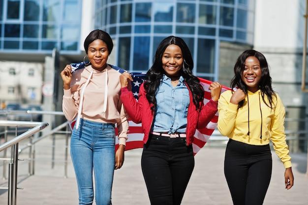 Drei junge college-afroamerikanerfrauenfreunde mit flagge der usa.