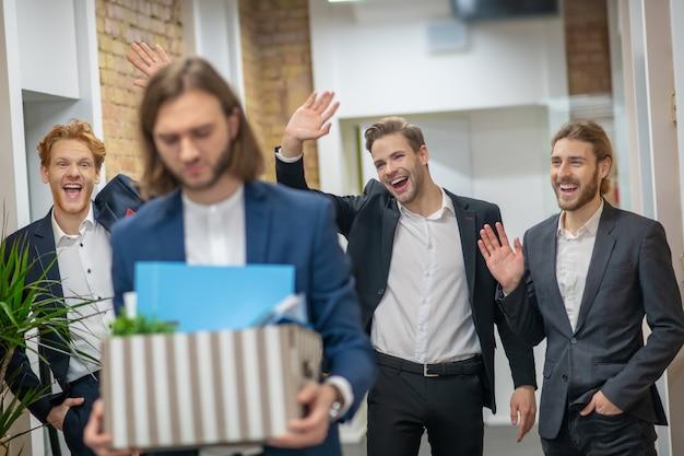 Drei junge erwachsene männer in anzügen, die darüber lachen, einen unglücklichen kollegen mit kiste im bürokorridor zu verlassen