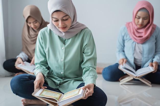 Drei junge frauen, die hijabs tragen, lesen das heilige buch des korans