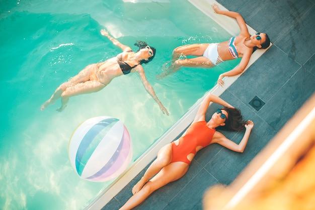 Drei junge frauen, die im swimmingpool sich entspannen