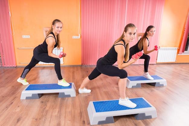 Drei junge frauen, die indoor-übungen mit hanteln und aeroben schritten machen und in die kamera schauen.