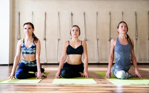 Drei junge frauen in der yogaklasse, die in der reihe sich entspannt sitzt, meditationshaltung machend