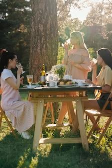 Drei junge frauen in freizeitkleidung, die getränke am servierten tisch nach dem abendessen im freien unter kiefer am sonnigen sommertag haben