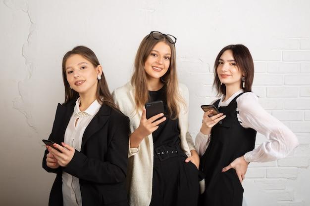 Drei junge frauen mit handys