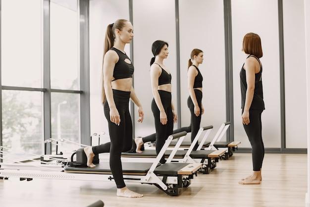 Drei junge frauen trainieren im fitnessstudio. frauen, die schwarze sportkleidung tragen. kaukasische mädchen trainieren mit ausrüstung.
