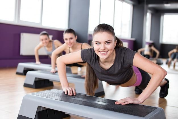 Drei junge frauen trainieren mit steppern im fitnessstudio.