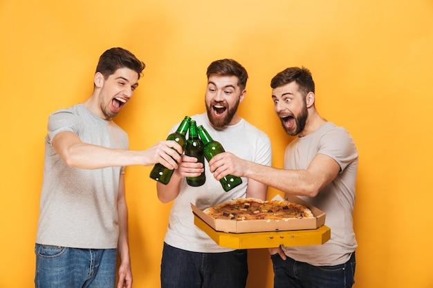 Drei junge freudige männer, die eine große pizza halten