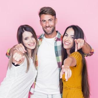 Drei junge freunde, die finger in richtung zur kamera gegen rosa hintergrund zeigen