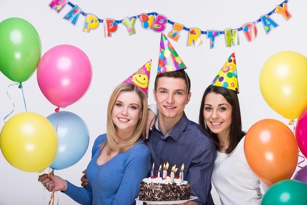 Drei junge freunde, die spaß auf geburtstagsfeier haben.