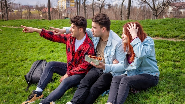Drei junge freunde sitzen auf dem gras und halten essen in einem park