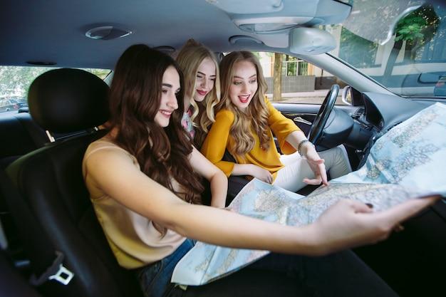 Drei junge freundinnen, die in ein auto reisen.