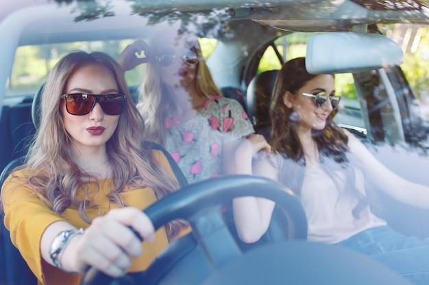 Drei junge freundinnen, die in ein auto reisen