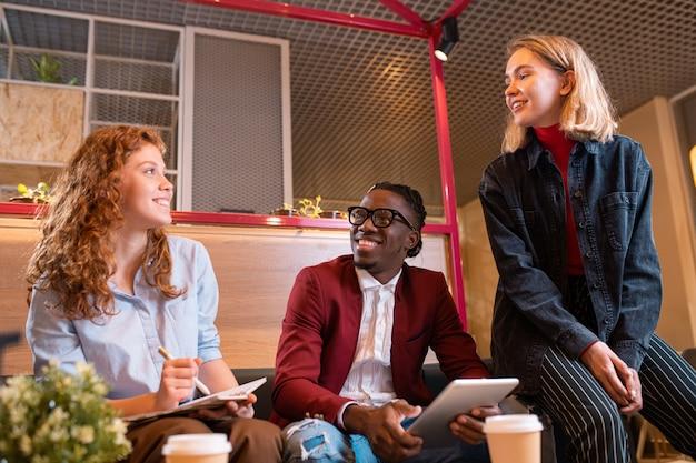 Drei junge fröhliche manager diskutieren arbeitsfragen beim treffen in einem zeitgenössischen café oder büro