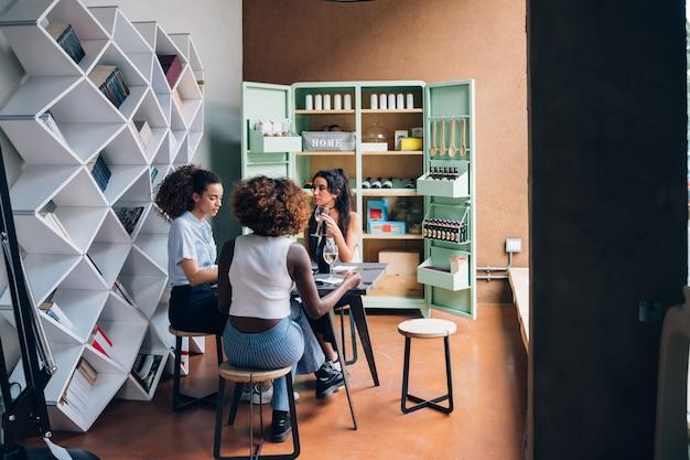 Drei junge gemischtrassige frauen, die im modernen restaurant zusammen trinkt sitzen