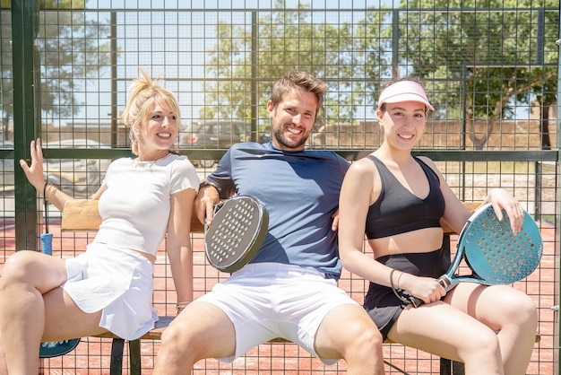 Drei junge glückliche lächelnde padel-tennisspieler nach einem spiel a