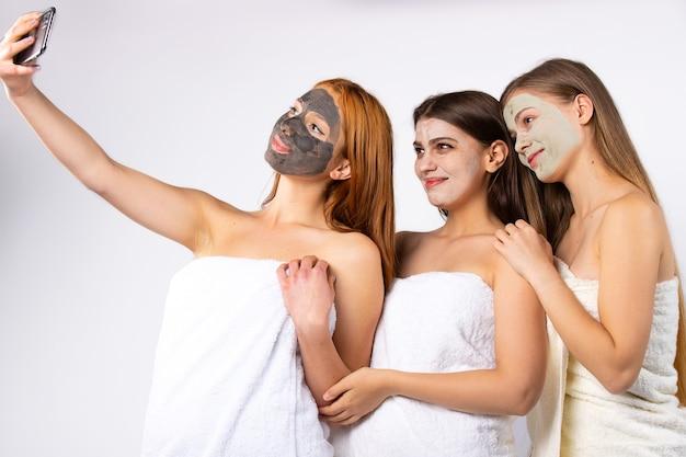 Drei junge glückliche mädchen mit gesichtsbehandlung, eingewickelt in handtücher, machen ein selfie. . hochwertiges foto