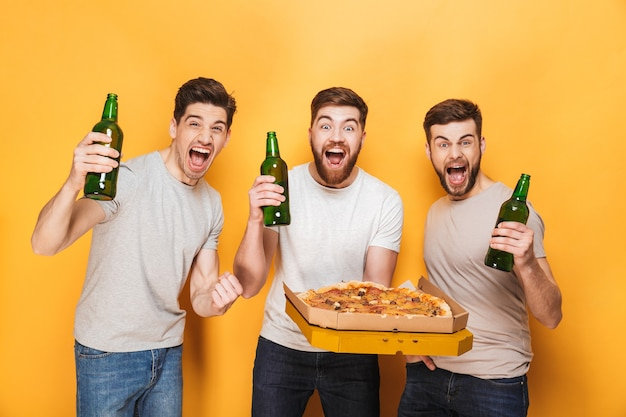 Drei junge glückliche männer, die eine große pizza halten