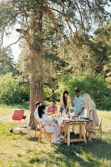 Drei junge interkulturelle leute, die daneben standen, servierten tisch und aßen und tranken, während ihre freunde in der nähe saßen und nach dem abendessen redeten