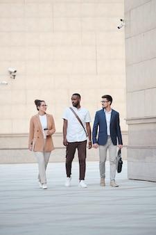 Drei junge interkulturelle manager unterhalten sich über ihre pläne für den abend, während sie sich im freien entlang großer zeitgenössischer gebäude bewegen