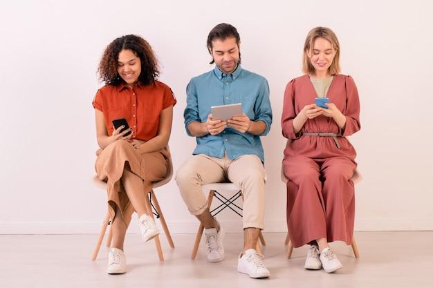 Drei junge interkulturelle menschen, die moderne mobile geräte verwenden und im internet surfen, während sie auf stühlen an der weißen wand sitzen