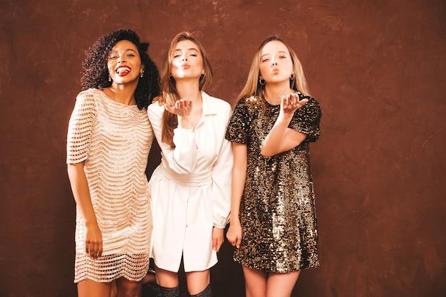 Drei junge internationale schöne brunettefrauen im modischen glänzenden sommerkleid.