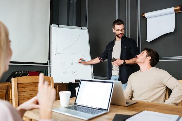 Drei junge kollegen sitzen bei der arbeit mit laptops und schreibtisch