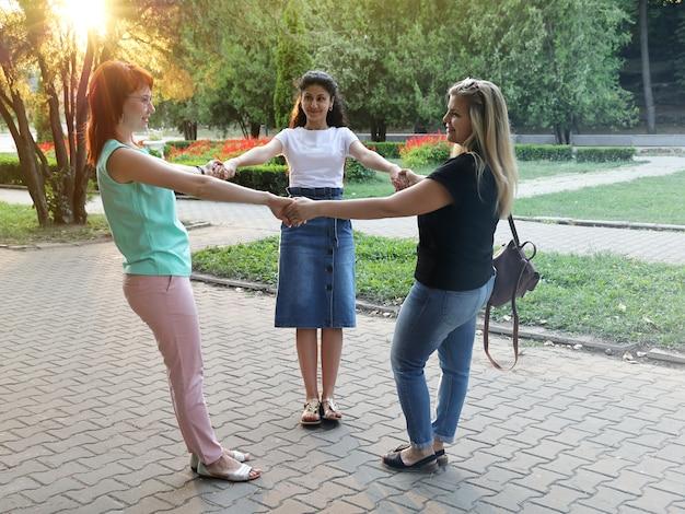 Drei junge lächelnde freundinnen halten hände im kreis in den strahlen