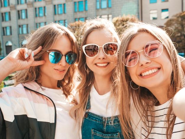 Drei junge lächelnde hippie-frauen in der sommerkleidung mädchen, die selfie selbstporträtfotos auf smartphone machen modelle, die in der straße aufwerfen frauen, die positive gesichtsgefühle zeigen