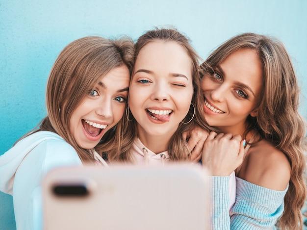 Drei junge lächelnde hippie-frauen in der sommerkleidung mädchen, die selfie selbstporträtfotos auf smartphone machen modelle, die in der straße nahe wand aufwerfen frauen, die positive gesichtsgefühle zeigen