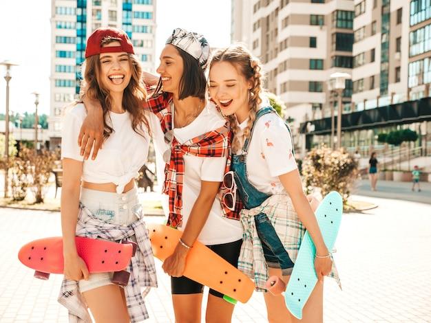 Drei junge lächelnde schöne mädchen mit bunten penny skateboards.