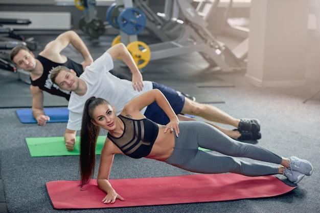 Drei junge leute, die seitenplanke üben, werfen während des yoga in der turnhalle auf.