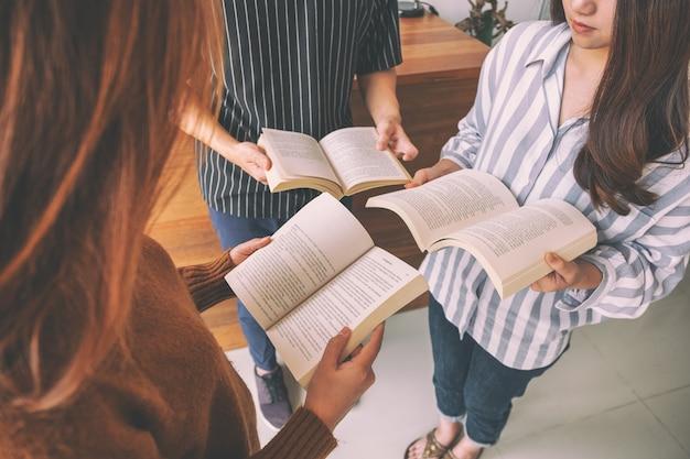 Drei junge leute standen im kreis und genossen es gemeinsam bücher zu lesen
