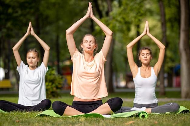 Drei junge mädchen beim yoga sitzen auf yogamatten auf grünem gras im park an einem warmen tag.