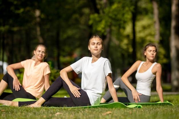 Drei junge mädchen, die sich auf yogamatten auf grünem gras im park im freien dehnen.
