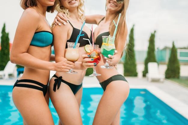 Drei junge mädchen haben spaß am pool, resorturlaub. gebräunte frauen entspannen sich im schwimmbad