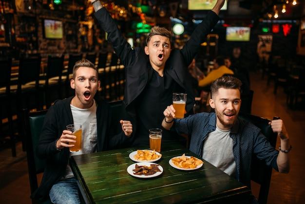 Drei junge männer feiern den spielsieg in einer sportbar, eine glückliche freundschaft der fußballfans