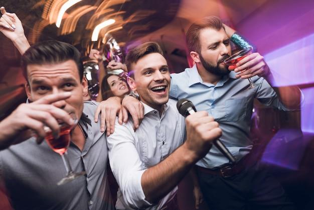 Drei junge männer singen in einem karaoke-club