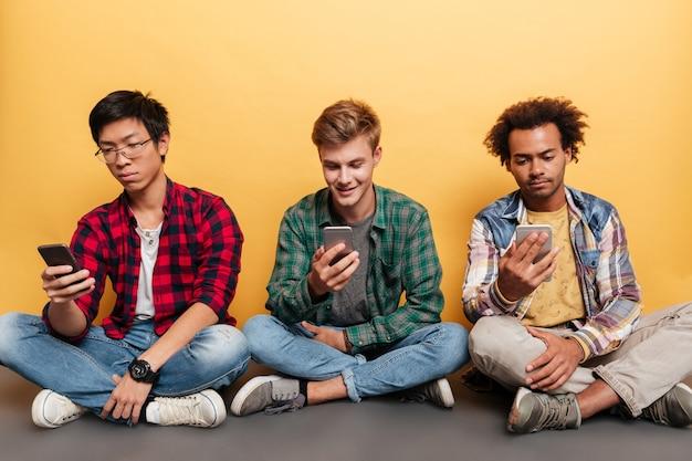 Drei junge männerfreunde sitzen und benutzen smartphone über gelbem hintergrund