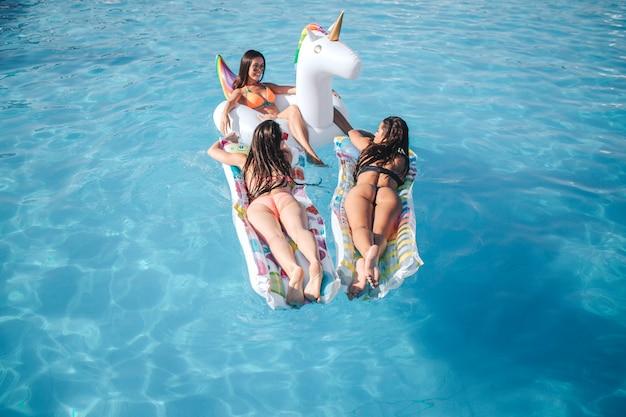 Drei junge modelle, die im schwimmbad aufwerfen. sie liegen auf schwimmern. zwei frauen zeigen ihre erstaunlichen körperformen. drittes model chillt und schaut ihre freunde an.