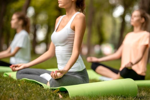 Drei junge schlanke mädchen sitzen in den lotuspositionen mit geschlossenen augen und machen an einem warmen tag yoga auf yogamatten auf grünem gras im park.