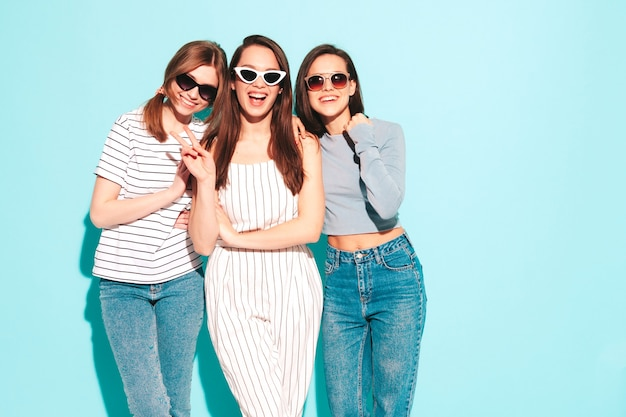 Drei junge schöne lächelnde hippie-frau in trendiger gleicher sommerkleidung